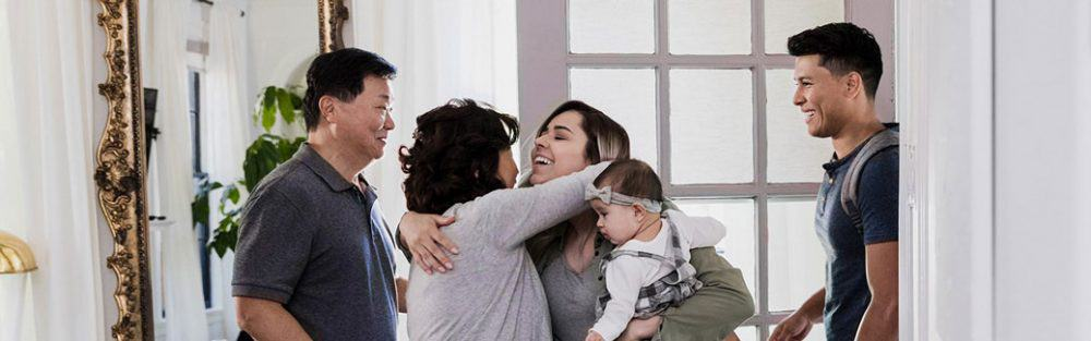 adult daughter, holding baby, hugging her mother while her father and husband look on.