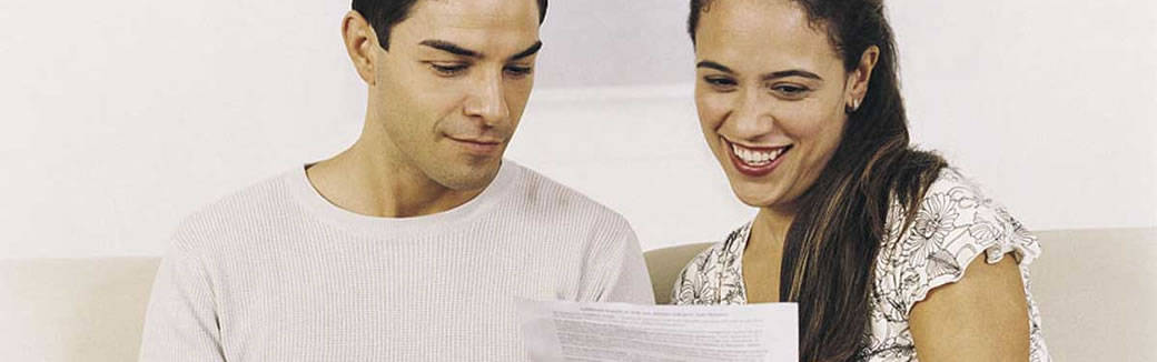 couple smiling looking at a piece of paper