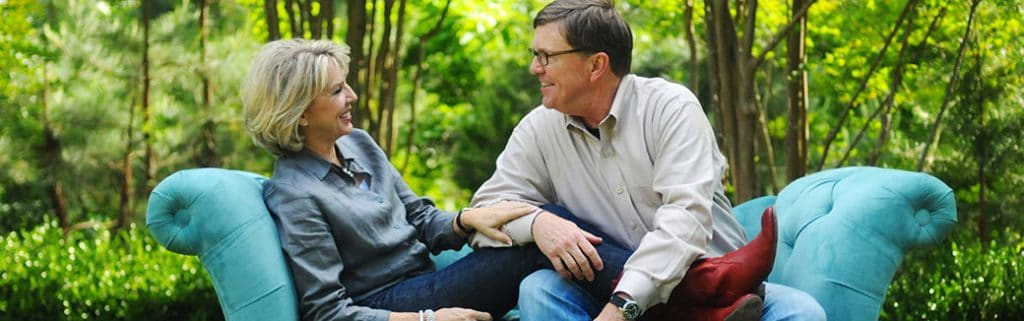 Barbara and Dennis Rainey looking at each other and smiling while sitting on a couch in a wooded area.