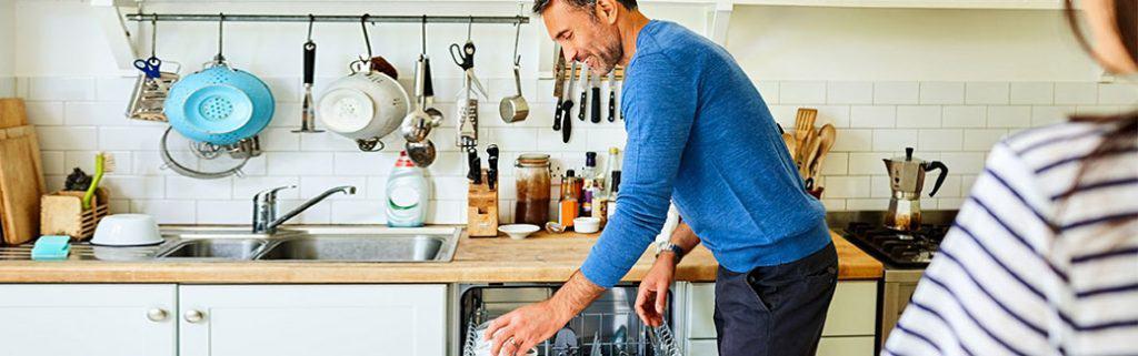 husband putting dishes in dishwasher