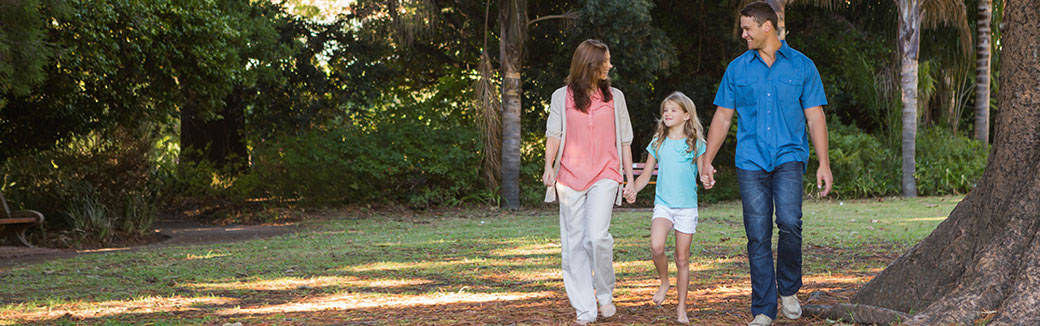 Mom and Dad walking with their daughter down a tree-lined path