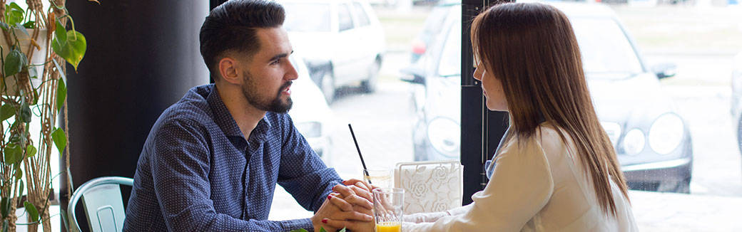 man and woman sitting at a table having a conversation