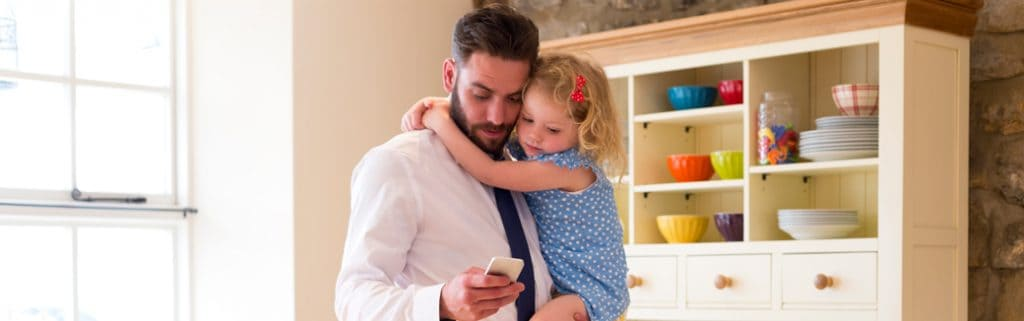 father holding daughter while checking his phone