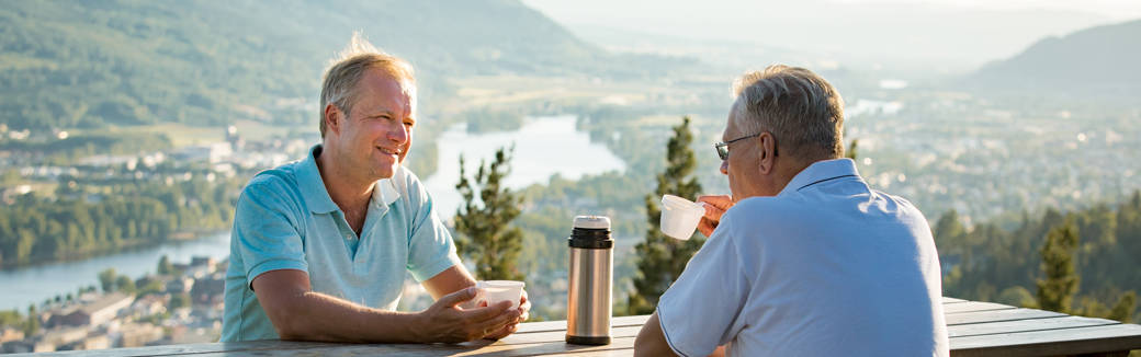 Two men sitting outside drinking coffee